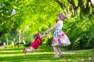 moeder en dochter spelen in een park foto