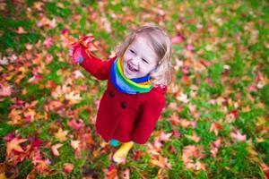 klein meisje spelen met esdoornblad in de herfst foto