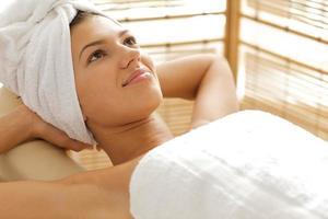 jonge vrouw ontspannen op massagetafel met handen beh