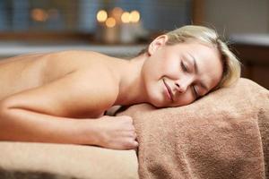 jonge vrouw liggend op een massagetafel in de spa foto