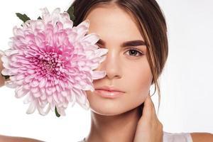 mooi meisje met chrysanthemum bloem op half gezicht