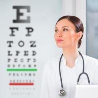 vrouwelijke opticien die zich voor gezichtsvermogenstest in het ziekenhuis bevindt foto