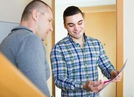 servicemedewerker met huurder bij deuropening foto