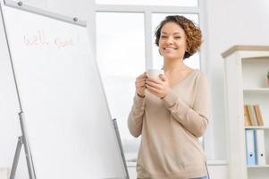 vrouwelijke werknemer drinkt koffie bij de flipboard foto