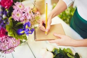 bloemist met blocnote en potlood foto