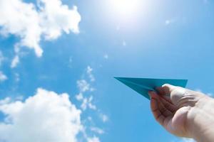 papieren vliegtuigje tegen bewolkte hemel foto