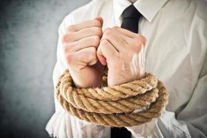 zakenman met handen vastgebonden in touwen foto