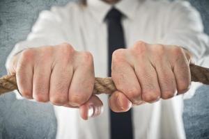 zakenman strak tegen een touw foto