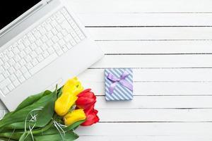 witte computer en boeket tulpen foto