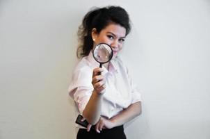 zakelijke vrouw houdt vergrootglas en een mobiele telefoon foto