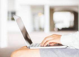 man te typen op een laptop buitenshuis foto