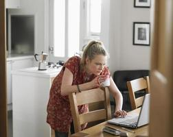 vrouw die koffie heeft terwijl het gebruiken van laptop foto