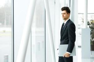 zakenman met laptop in de buurt van het raam na te denken over de toekomst foto