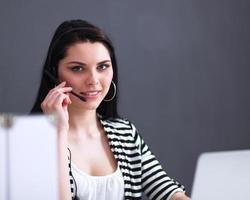 mooie bedrijfsvrouw die bij haar bureau met hoofdtelefoon werkt en foto