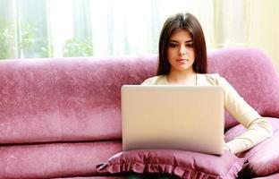 mooie vrouw zittend op de bank en met behulp van laptop foto