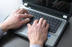 zakenman handen op laptop toetsenbord foto
