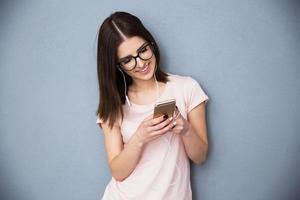 vrouw die smartphone met hoofdtelefoons gebruiken foto