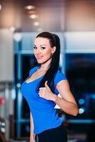 gelukkig lachende vrouw op de weegschaal op sportschool foto
