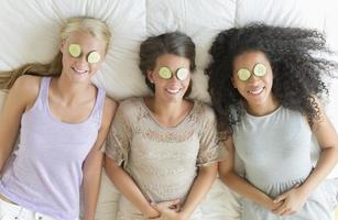 gelukkig tienermeisjes met plakjes komkommer op hun ogen foto