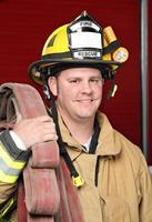 een knappe brandweerman lachend naar de camera