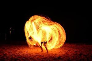 geweldige vuurshow vlammende paden 's nachts op het strand, thailand foto