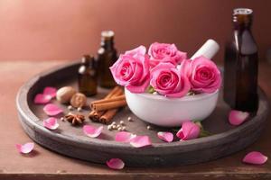 spa en aromatherapie set met roze bloemen mortel, kruiden foto