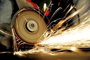 werknemer snijden metaal met molen foto
