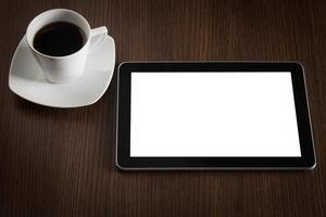 tablet en kopje koffie op kantoor tafel. foto