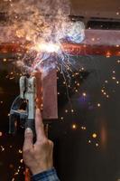 lassen van staal met verspreide vonk die rook verlicht foto