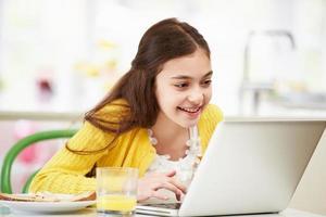 Spaans meisje dat laptop met behulp van die ontbijt eet foto