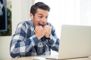 vrolijke man kijken naar het spel op zijn laptop