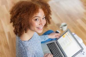 zwarte Afro-Amerikaanse student meisje met behulp van een laptop foto