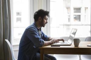 Aziatische man thuis werken op laptop. foto