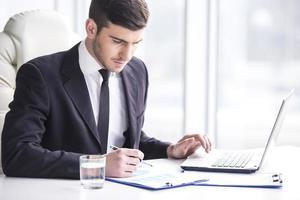zakenman zittend aan een tafel met pen en papier en laptop foto