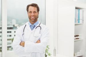 lachende arts met gekruiste in medische kantoor armen foto