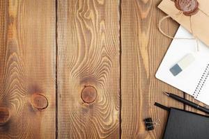 houten tafel met Kladblok en vintage envelop foto