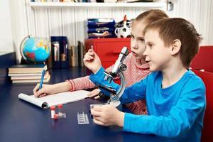meisje en jongen onderzoekt medicijn voor microscoop foto
