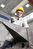 metaalbewerker werkt metaal met hamer op het aambeeld foto