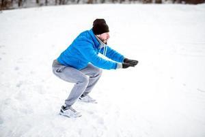 atletische man doen sit-ups op sneeuw, tijdens de training foto