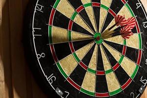 de darts geïsoleerd op houten achtergrond foto