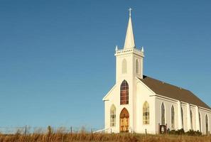 witte land kerk over een weide op een wolkenloze hemel foto