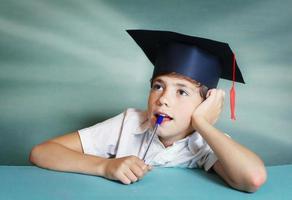 jongen in afstuderen pet denken over schoolvak foto