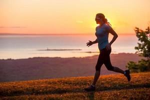 eenzame vrouw trail loopt in de buurt van een watermassa foto