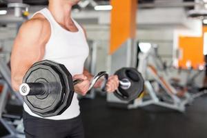 aantrekkelijke jonge sporter is training in het fitnesscentrum foto