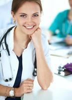 mooie jonge glimlachende vrouwelijke arts zitten aan de balie foto