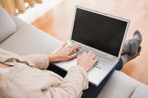 blonde vrouw die laptop op laag met behulp van foto