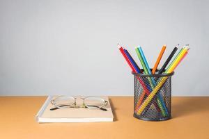 stapel kleurpotloden en glazen op notitieboekje foto