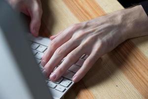 close up van het typen van man handen foto