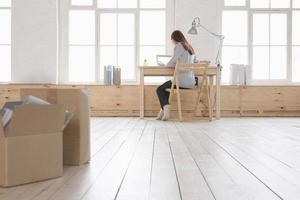 vrouw met behulp van laptop aan balie in loft appartement foto