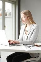 portret van mooie zakenvrouw die op laptop werkt foto